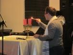 Pastor Krzysztof zapala świece na chanukiji